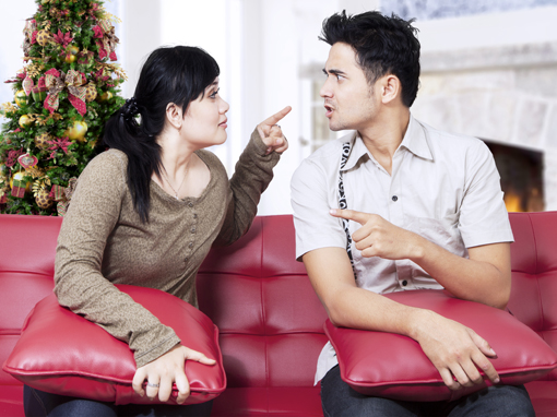Portrait of couple quarreling, pointing, and blaming each other at home in christmas day