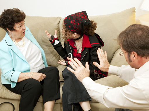 Teen girl yelling at her mother during a family counseling session.